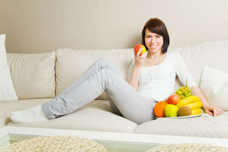Young woman eating an apple on a couch photo