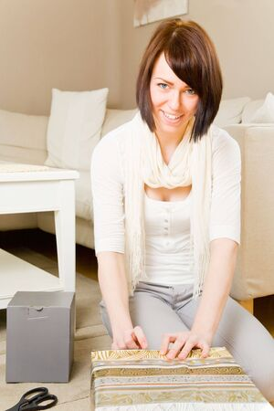 Young woman packing presents in her living room photo
