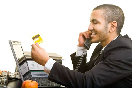 Business man with his laptop and a credit card on the phone photo