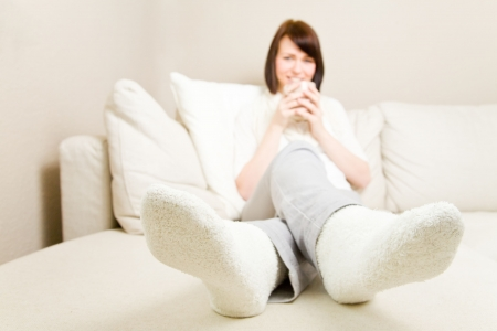 warm color: Young woman drinking hot coffee and resting her feet