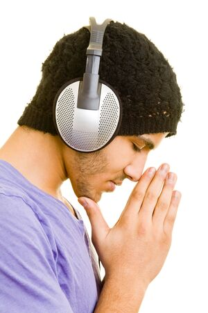 Man listening to music with headphones while praying photo