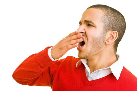 covering mouth: Young man is yawning and holding his hand in front of his mouth