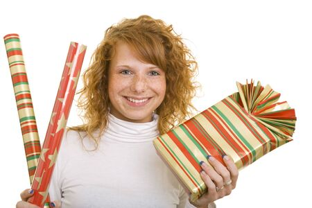Young redhaired woman holding a gift and wrapping paper photo