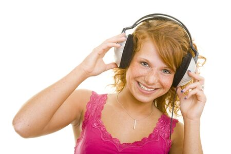 Young redhaired woman listing to music over headphones photo