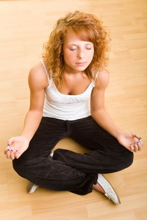 getting late: Young redheaded woman sitting and meditating