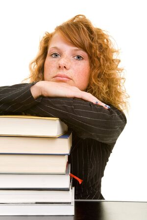 Young redhaired woman leaning over books photo