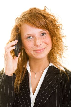 Young redhaired woman listening to her mobile phone photo