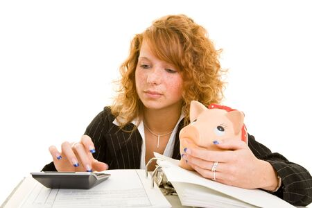 gripping hair: Young redhaired woman with piggy bank, files and a calculator