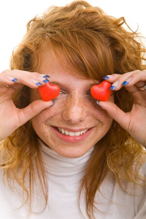 Young redhaired woman holds two heart shaped candy pieces in front of her eyes photo