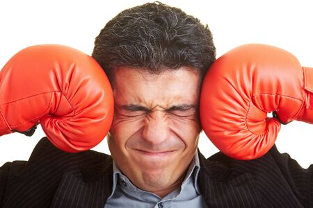 strains: Business man pressing red boxing gloves against his head