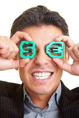 greed: Businessman holding a Dollar and a Euro-sign in front of his eyes