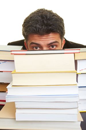 Man hiding behind a stack of books photo