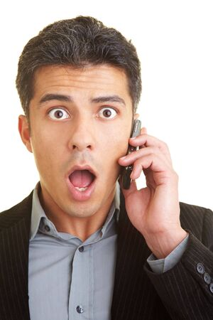 Businessman with cell phone looks shocked photo