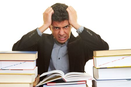 industriousness: Businessman with many books pulling his hair