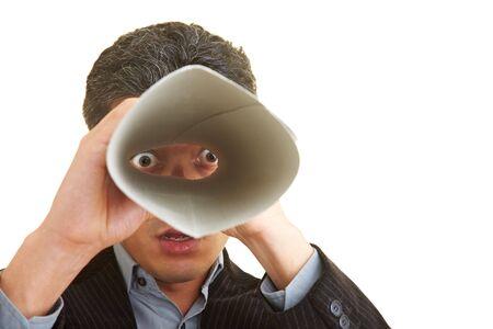 Businessman looking through a speaking tube photo
