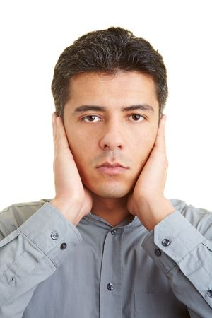 coward: Man covering his ears with his hands Stock Photo