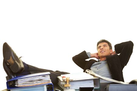 arms behind head: Businessman leaning back and putting his feet on his desk Stock Photo