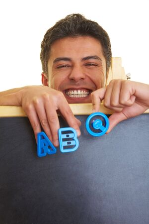 Happy man behind blackboard holding the letters ABC photo