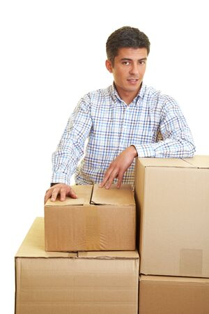 cajas de carton: Hombre de pie detr�s de una pila de cajas de cart�n Foto de archivo