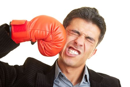 attacking: Business man hitting himself with a red boxing glove in the face