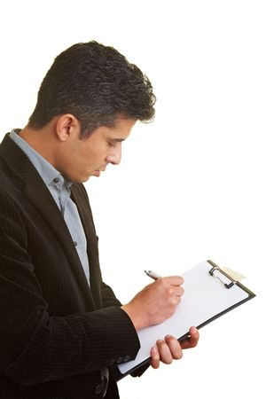 making notes: Businessman making notes on a clipboard