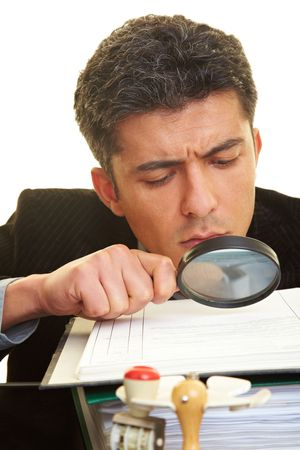 skepticism: Businessman with magnifying glass reading the fineprint in a contract