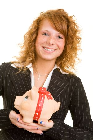 Young redhaired woman in a business suit carrying a big piggy bank photo