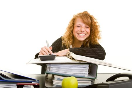 smirking: Young redhaired woman is smirking while working on her desk