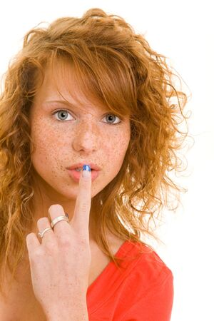Young redhaired woman putting her index finger in front of her mouth photo