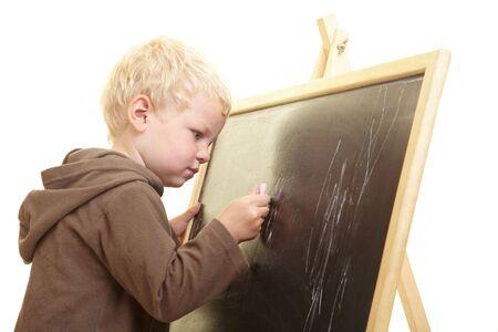 Little boy drawing on a blackboard photo