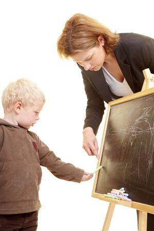 Boy drawing on a blackboard photo