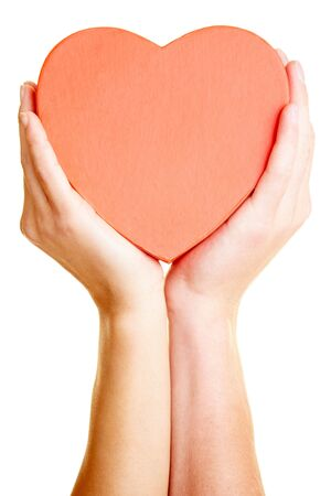 hands together: Two hands holding a big red heart