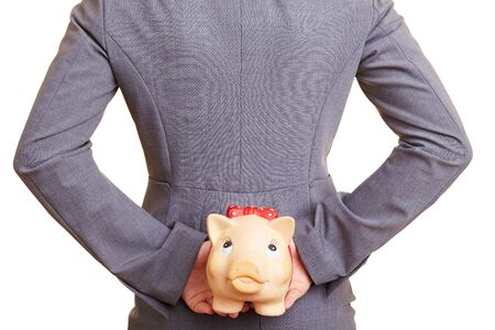 tax evasion: Businesswoman hiding a piggy bank behind her back Stock Photo