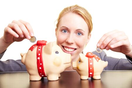 Businesswoman dropping coins in two piggy banks photo
