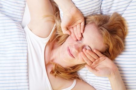 insomnio: La mujer se frotaba los ojos despu�s de despertar