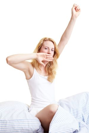 stretch out: Happy blond woman sitting in her bed