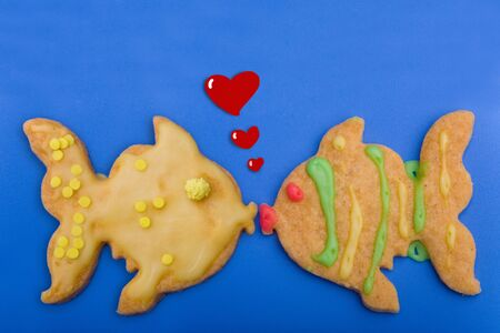 Two cookie fish kiss each other with hearts coming up photo
