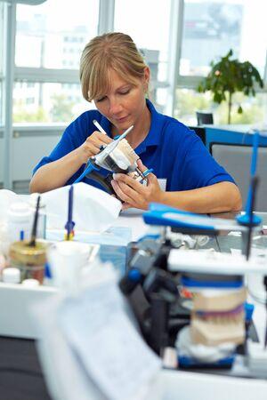 Dental technician layering ceramics for dentures in an articulator photo