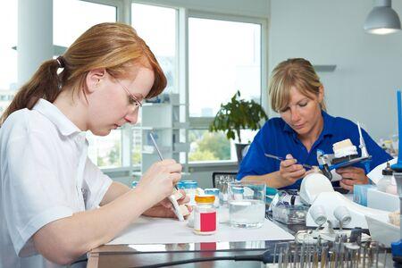 apprenti: Deux techniciens dentaires travaillent dans un laboratoire dentaire