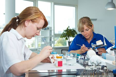 Two dental technicians working in a dental laboratory photo