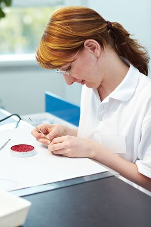 Dental technician working on a cap for a tooth Stock Photo - 5835581