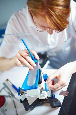 articulator: Dental technician working on dentures with an articulator
