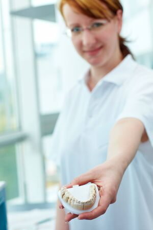 Dental technician showing a ceramic inlay in a lab photo