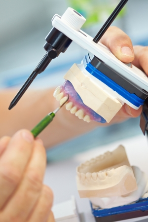 Dental technician working with probe and articulator photo