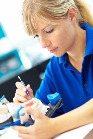 laboratorio dental: Prot�sico dental trabajando en pr�tesis dentales con un articulador Foto de archivo