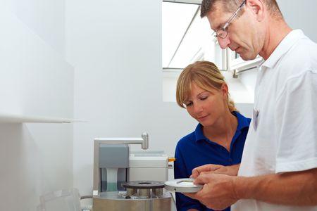 Dental technician explaining a pin drill unit photo
