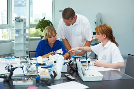 lab technician: Three dental technicians working in a dental laboratory