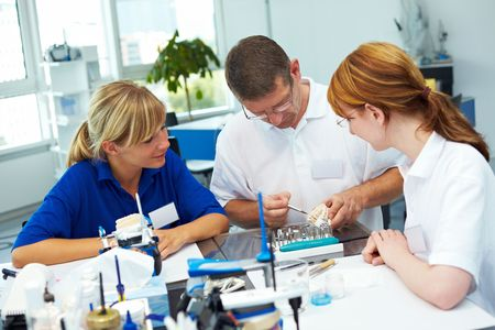 Three dental technicians working in a dental laboratory photo