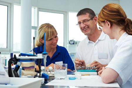 laboratorio dental: Tres t�cnicos dentales, trabajando en un laboratorio dental
