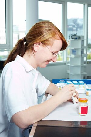 Dental technician working on ceramic inlays in a lab photo